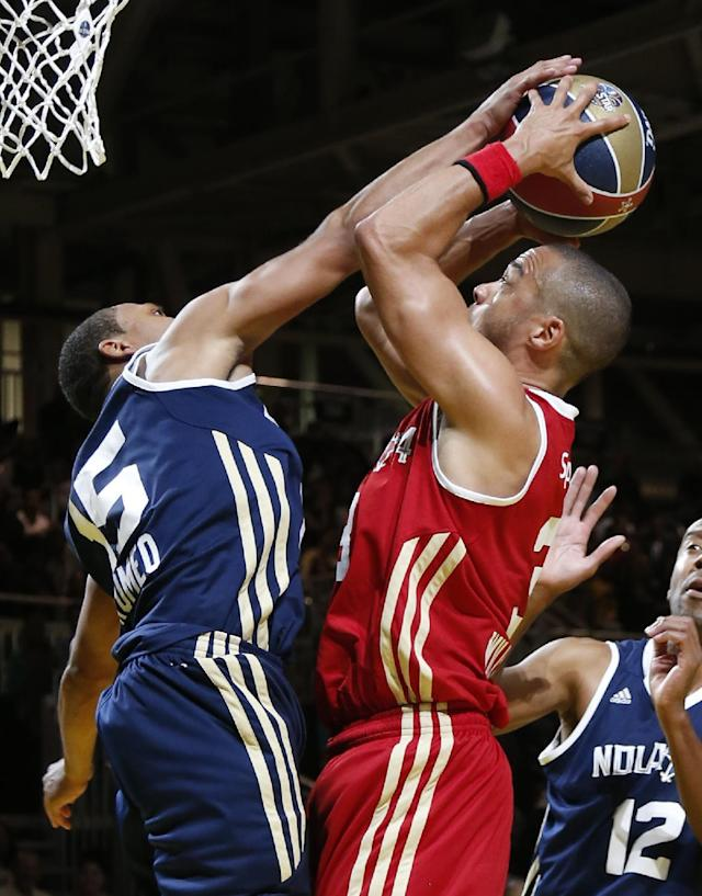 East's Romeo Miller (15) blocks the shot of West's Jesse Williams (3) in the second half as they participate in the NBA All-Star Celebrity basketball game in New Orleans, Friday, Feb. 14, 2014. East won 60-56. (AP Photo/Bill Haber)