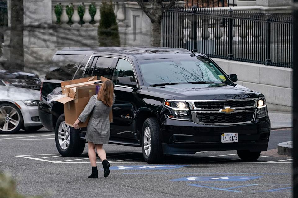A woman carries boxes out of the White House's West Wing in Washington DC on January 15, 2021.