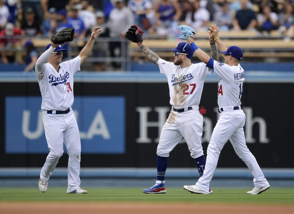 From left to right, Los Angeles Dodgers' Joc Pederson, Alex Verdugo and Enrique Hernandez celebrate after theydefeated the Philadelphia Phillies in a baseball game Sunday, June 2, 2019, in Los Angeles. (AP Photo/Mark J. Terrill)