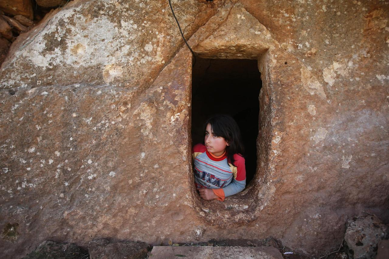 Nihal, 9, looks at the entrance of an underground Roman tomb used as shelter from Syrian government forces shelling and airstrikes, at Jabal al-Zaweya, in Idlib province, Syria, Thursday Feb. 28, 2013. Across northern Syria, rebels, soldiers, and civilians are making use of the country's wealth of ancient and medieval antiquities to protect themselves from Syria's two-year-old war. They are built of thick stone that has already withstood centuries, and are often located in strategic locations overlooking towns and roads. (AP Photo/Hussein Malla)