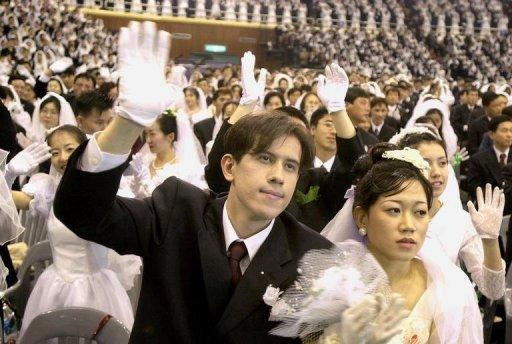 Couples wave during a mass wedding organised by Sun Myung Moon's Unification Church in Seoul in 2002. The church was famed for its mass weddings that married thousands of followers in sports stadia ceremonies led by Moon