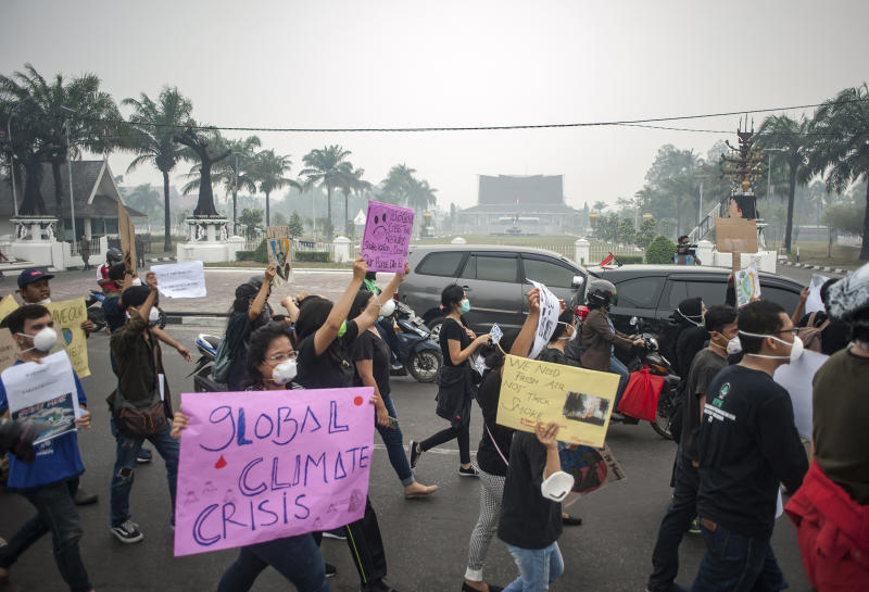 Activists hold posters as they march during a protest urging the government to speed up their action to tackle forest fires in Palangkaraya, Central Kalimantan, Indonesia, Friday, Sept. 20, 2019. Haze blown by monsoon winds from fires in Indonesia has begun affecting some areas of the Philippines and raised concerns about aviation safety and possible health risks, an official said Friday. (AP Photo/Fauzy Chaniago)