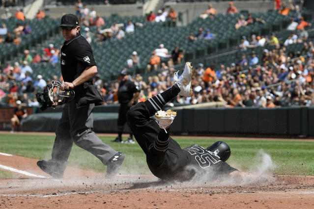 Home plate umpire Lance Barksdale, left, watches as Baltimore Orioles' Anthony Santander, right, slides home to score on a double by Renato Nunez during the third inning of a baseball game against the Tampa Bay Rays, Sunday, Aug. 25, 2019, in Baltimore. (AP Photo/Nick Wass)