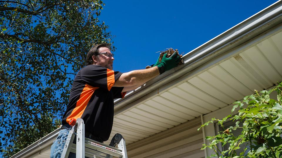 Worker cleaning gutters on a customers home.