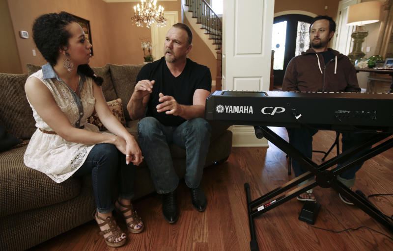 """In this May 13, 2013 photo, country singer Trace Adkins, center, talks with Maureen Maltez as they rehearse the song """"Watch the World End"""" in Franklin, Tenn. Atkins recently heard Maltez sing at a junior college fundraiser, and asked her to sing with him at some upcoming appearances in New York. At right is keyboard player Jon Coleman. (AP Photo/Mark Humphrey)"""