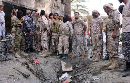 Members of security forces organized by the Saudi-led coalition gather at the site of a suicide car bomb attack outside a police forces camp in Aden