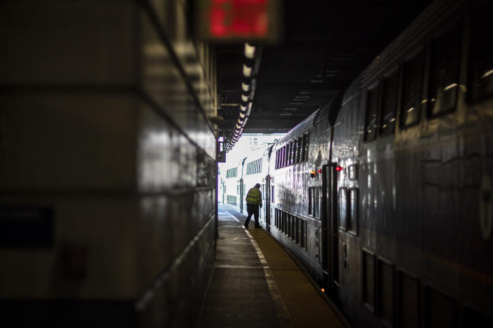 A train employee boards the commuter rail heading to Boston after waiting for passengers, Friday, Nov. 20, 2020, in Providence, R.I. With the coronavirus surging out of control, the nation's top public health agency pleaded with Americans not to travel for Thanksgiving and not to spend the holiday with people from outside their household. (AP Photo/David Goldman)