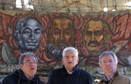 Laurent Levi-Strauss and Graham Bell, experts at heritage organisation Europa Nostra and Mario Aymerich, technical consultant of the European Investment Bank Institute stand in front of mosaics depicting founders and leaders of the Bulgarian Communist Party at Buzludzha Monument, Stara Planina mountain, September 27, 2018.  REUTERS/Stoyan Nenov