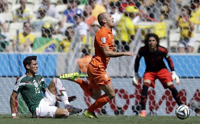 Netherlands' Arjen Robben, right, goes down under a challenge from Mexico's Hector Moreno during the World Cup round of 16 soccer match between the Netherlands and Mexico at the Arena Castelao in Fortaleza, Brazil, Sunday, June 29, 2014. (AP Photo/Natacha Pisarenko)