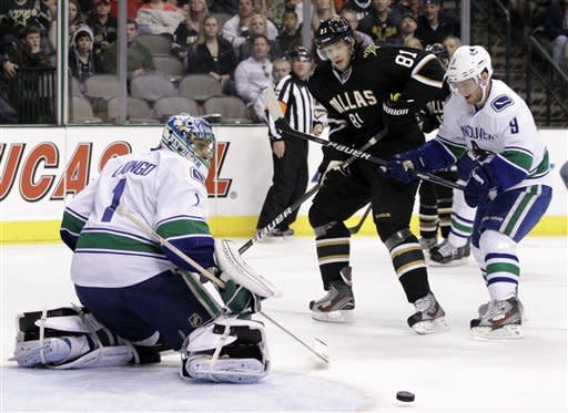 Vancouver Canucks' Roberto Luongo (1) keeps his eyes on a puck cleared by teammate Cody Hodgson (9) as Dallas Stars' Tomas Vincour (81), of the Czech Republic, pressures in the first period of an NHL hockey game on Sunday, Feb. 26, 2012, in Dallas. (AP Photo/Tony Gutierrez)