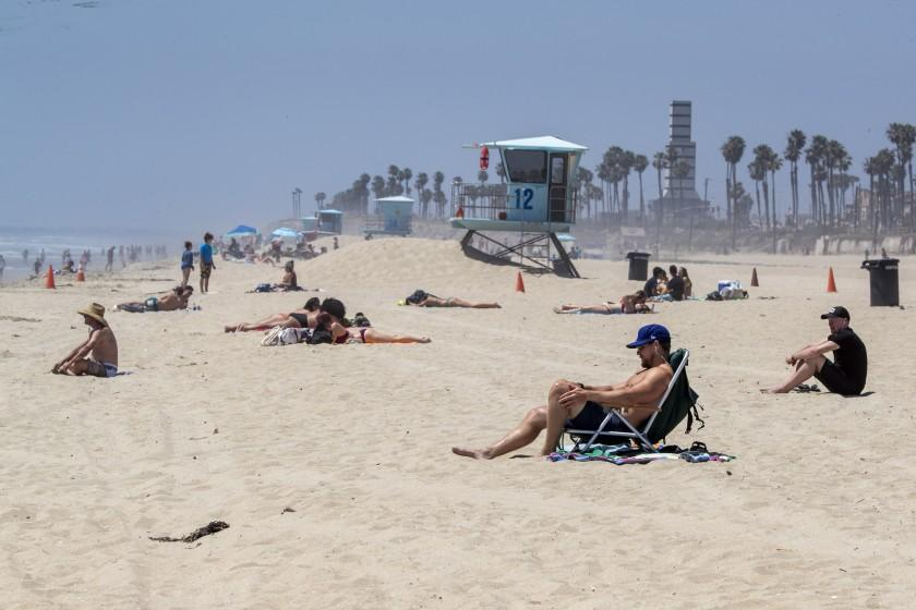 """Sunbathers at Huntington Beach on Sunday flout Gov. Newsom's active-use-only order. <span class=""""copyright"""">(Allen J. Schaben / Los Angeles Times)</span>"""