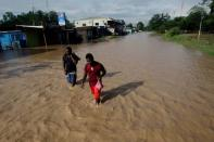 Men walk along a street flooded by the Chamelecon River due to heavy rain caused by Storm Iota, in La Lima