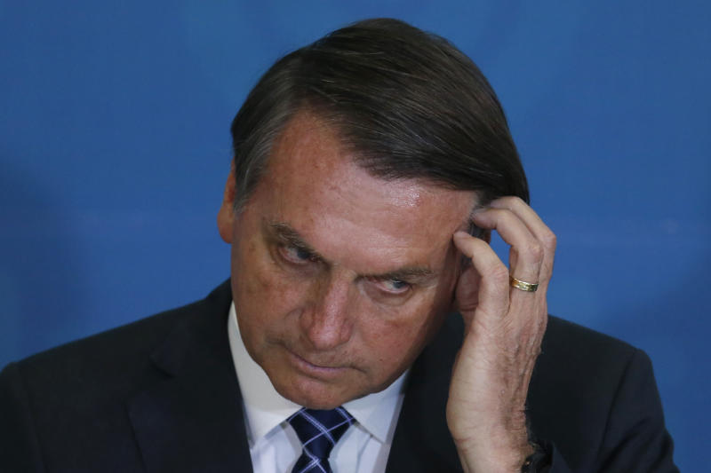 Brazil's President Jair Bolsonaro scratches the side of his head during a ceremony at the Planalto Presidential Palace, in Brasilia, Brazil, Monday, Dec. 2, 2019. Brazilian President Jair Bolsonaro's U.S.-focused foreign policy efforts have suffered a setback after Donald Trump threatened to impose tariffs on steel and aluminum on the South American nation. (AP Photo /Eraldo Peres)
