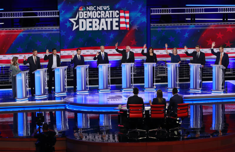 Democratic presidential candidates left to right, author Marianne Williamson, former Colorado Gov. John Hickenlooper, entrepreneur Andrew Yang, South Bend Mayor, Pete Buttigieg, former Vice-President Joe Biden, Sen. Bernie Sanders, I-Vt, Sen. Kamala Harris, D-Calif., Sen. Kristen Gillibrand, D-NY., former Colorado Sen. Michael Bennet and Rep. Eric Swalwell, D-Calif. raise their hands when asked if they would provide healthcare for undocumented immigrants, during the Democratic primary debate hosted by NBC News at the Adrienne Arsht Center for the Performing Arts, Thursday, June 27, 2019, in Miami. (AP Photo/Wilfredo Lee)
