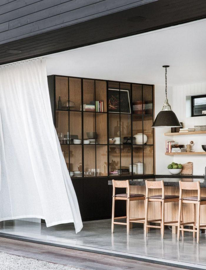 <p>This kitchen designed by Amber Interiors is California dream. With a floor-to-ceiling, wall-to-wall door that leads outside, you can enjoy the fresh air at all times. Plus, the light sheers blowing in the wind add an ethereal vibe. Pro tip: Customize glass cabinetry that stretches up to the feeling so it'll feel even more open.</p>