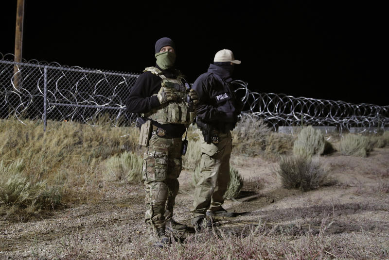"Police officers guard an entrance to the Nevada Test and Training Range near Area 51, Sept. 20, 2019, near Rachel, Nev. People gathered at the gate inspired by the ""Storm Area 51"" internet hoax. (Photo: John Locher/AP)"