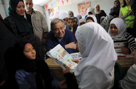 United Nations Secretary General Antonio Guterres (C) speaks to Syrian refugees during his visit to Al Zaatari refugee camp in the Jordanian city of Mafraq, near the border with Syria