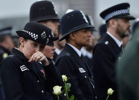 A police officer wipes her face as she holds a rose during an event to mark one week since a man drove his car into pedestrians on Westminster Bridge then stabbed a police officer in London, Britain March 29, 2017. REUTERS/Hannah McKay