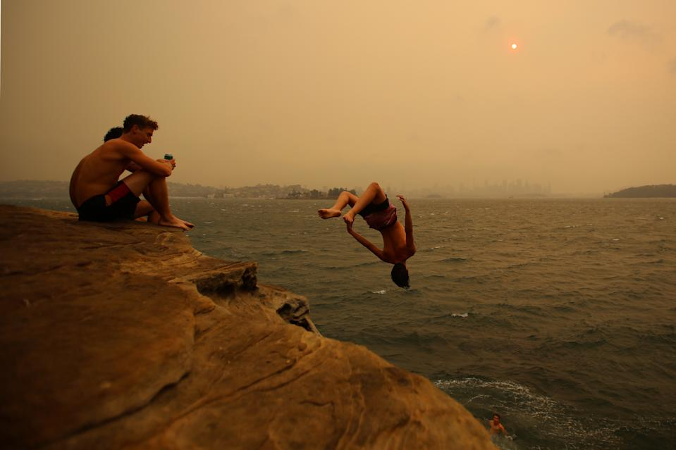 Smoke haze from bushfires blankets the Sydney CBD as beachgoers Jump from a cliff in Nielsen Park.