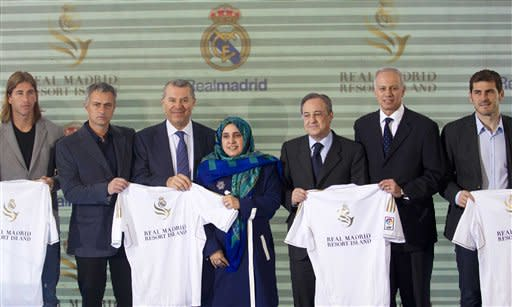 Real Madrid management and players pose with a United Arab Emirates delegation at the Bernabeu stadium in Madrid Thursday March 22, 2012. Real Madrid will open a Sports oriented theme park combining soccer and tourism in The United Arab Emirates in 2015 which will include sports facilities, hotels, apartments, bungalows and a beach resort. Left to right; Sergio Ramos, coach Jose Mourinho from Portugal, Dr Khater Massaad, CEO of RAK Investment Authority and advisor to Sheikh Saud Bin Saqr Al Qassimi, The United Arab Emirates embassador to Spain, Hissa Abdulla Ahmed Al-Otaiba, Real Madrid's president Florentino Perez, Lous Armand de Rouge, CEO of RAK Investments and goalkeeper Iker Casillas. (AP Photo/Paul White)