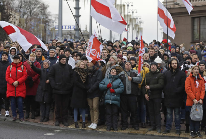 Protesters wait for a green light to cross the street as they attend a procession in downtown Minsk, Belarus, Sunday, Dec. 8, 2019. A rally was held to protest closer integration with Russia which protesters fear could erode the post-Soviet independence of Belarus, a nation of 10 million. (AP Photo/Sergei Grits)