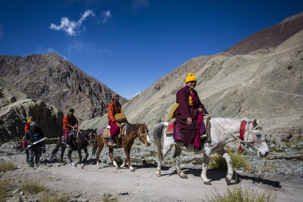 A Buddhist monk travels by horse with his companions near the village of Rumbak.