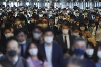 A station passageway is crowded with commuters wearing face masks to help curb the spread of the coronavirus during a rush hour in Tokyo Friday, Nov. 20, 2020. (AP Photo/Eugene Hoshiko)