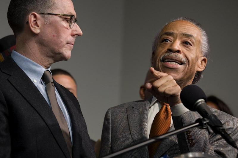 FILE - In this Tuesday, Oct. 29, 2013, file photo, the Rev. Al Sharpton, standing with Mark Lee, left, CEO of Barneys New York, addresses member of the media, at the National Action Headquarters in New York, after they and other community leaders discussed allegations of racial profiling. Two black customers recently claimed they were detained by police on suspicion of credit card fraud after lawfully purchasing expensive items. (AP Photo/Craig Ruttle, File)