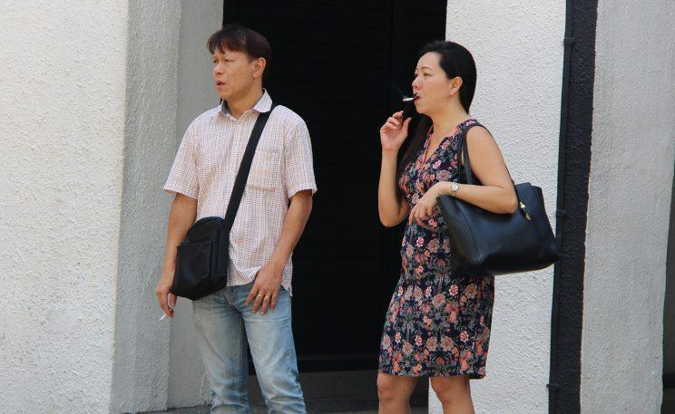 Two people smoking outside Cuppage Terrace, located at Orchard Road on Friday (30 June) afternoon. (Photo: Gabriel Choo/ Yahoo Singapore)