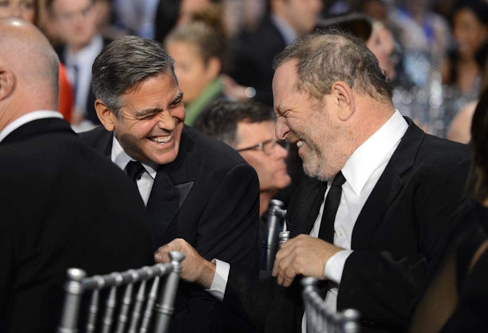 """George Clooney and Harvey Weinstein share a laugh in 2013. Clooney called the accusations against Weinstein """"disturbing"""" in part because many people may have covered them up. (Michael Kovac via Getty Images)"""
