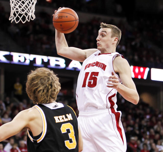 Wisconsin's Sam Dekker (15) pulls down a defensive rebound away from Milwaukee's Kyle Kelm during the first half of an NCAA college basketball game on Wednesday, Dec. 11, 2013, in Madison, Wis. (AP Photo/Andy Manis)
