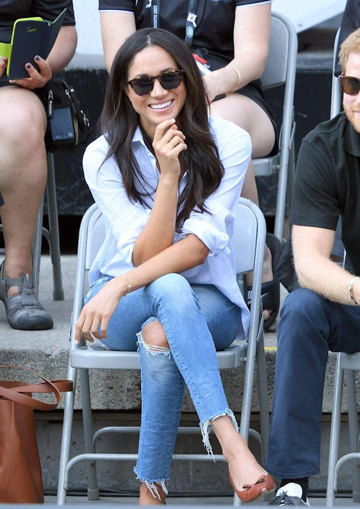 """<p>Before Meghan Markle was a royal, she wore <a href=""""https://www.vanityfair.com/style/2020/01/misha-nonoo-husband-shirt-meghan-markle"""" rel=""""nofollow noopener"""" target=""""_blank"""" data-ylk=""""slk:ripped jeans and a Misha Nonoo &quot;Husband&quot; shirt"""" class=""""link rapid-noclick-resp"""">ripped jeans and a Misha Nonoo """"Husband"""" shirt</a> to the Invictus Games with Prince Harry in 2017. The outing marked the couple's first public appearance together and showcased the power of """"<a href=""""https://www.glamour.com/story/women-who-shop-because-of-meghan-markle"""" rel=""""nofollow noopener"""" target=""""_blank"""" data-ylk=""""slk:The Markle Sparkle"""" class=""""link rapid-noclick-resp"""">The Markle Sparkle</a>,"""" as the shirt <a href=""""https://www.huffpost.com/entry/meghan-markle-husband-shirt_l_5e66876ac5b6670e72fc9b22"""" data-ylk=""""slk:promptly sold out"""" class=""""link rapid-noclick-resp"""">promptly sold out</a>. </p>"""
