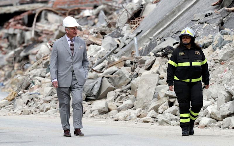 Britain's Prince Charles walks with a firefighter by the rubble of the 2016 earthquake-hit town of Amatrice, central Italy, Sunday, April 2, 2017. - Credit: Andrew Medichini/AP