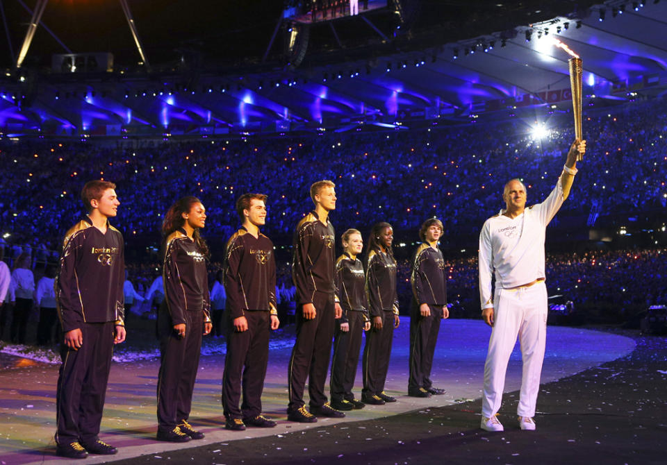 After being passed the torch by Olympic legend Steve Redgrave, seven young British athletes received flames from seven Olympians and then simultaneously lit over 200 miniature torches that rose together to form the Olympic cauldron at the London 2012 Olympics Opening Ceremony on Saturday, July 28, 2012. (AP Photo/Cameron Spencer, Pool)