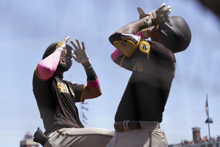 San Diego Padres' Fernando Tatis Jr., left, celebrates after hitting a two-run home run with Manny Machado during the second inning of a baseball game against the San Francisco Giants in San Francisco, Sunday, May 9, 2021. (AP Photo/Jeff Chiu)
