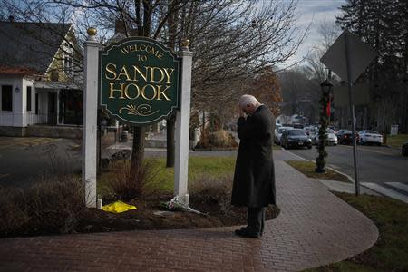 New Jersey resident Steve Wruble, who was moved to drive out to Connecticut to support local residents, grieves for victims of an elementary school mass shooting at the entrance to Sandy Hook village in Newtown, Connecticut in this December 15, 2012 file photo. REUTERS/Adrees Latif/Files