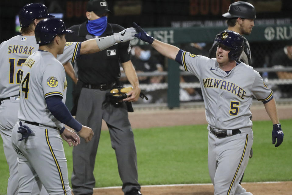 Milwaukee Brewers' Jedd Gyorko, right, celebrates with Justin Smoak, left, and Avisail Garcia after hitting a two-run home run against the Chicago White Sox during the fifth inning of a baseball game in Chicago, Thursday, Aug. 6, 2020. (AP Photo/Nam Y. Huh)