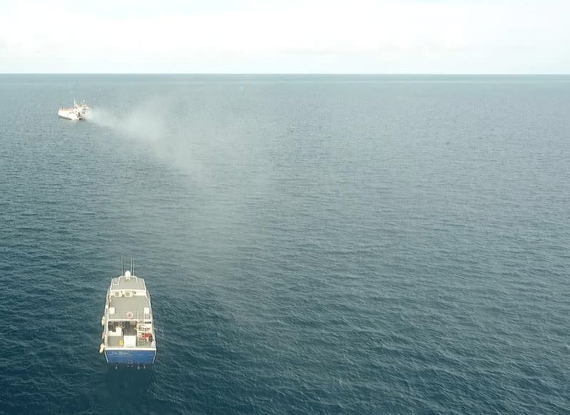 Plume from a seawater sprayer is seen during the second field trial at Broadhurst Reef on the Great Barrier Reef