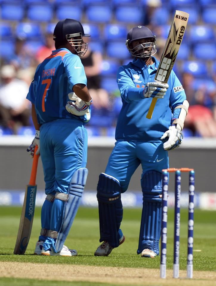 India's Dinesk Karthik (R) stands beside captain Mahendra Singh Dhoni as he celebrates his half century (50 Runs) during the warm-up cricket match ahead of the 2013 ICC Champions Trophy between India and Australia at The Cardiff Wales Stadium in Cardiff, Wales on June 4, 2013.  India won the toss and elected to bat first.  AFP PHOTO/Paul ELLIS        (Photo credit should read PAUL ELLIS/AFP/Getty Images)