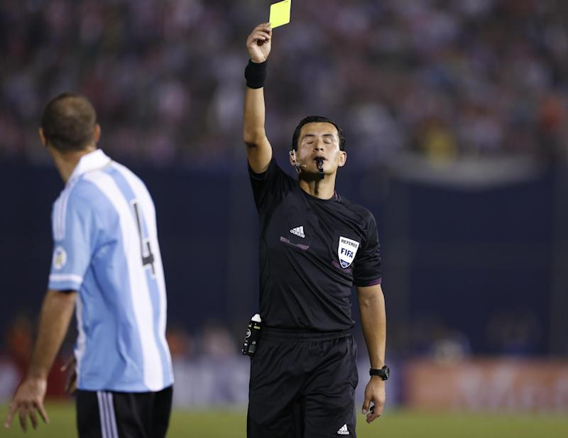 Referee Enrique Roberto Osses from Chile  shows a yellow card to Argentina's Pablo Zabaleta during a World Cup qualifying soccer game  against Paraguay in Asuncion, Paraguay, Tuesday, Sept. 10, 2013