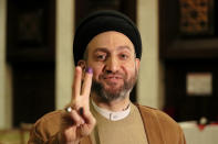 Ammar al-Hakim, leader of the Hikma political block, shows a v-sign with his ink-stained finger during the parliamentary elections in Baghdad, Iraq, Sunday, Oct. 10, 2021. Iraq closed its airspace and land border crossings on Sunday as voters headed to the polls to elect a parliament that many hope will deliver much needed reforms after decades of conflict and mismanagement. (AP Photo/Khalid Mohammed)