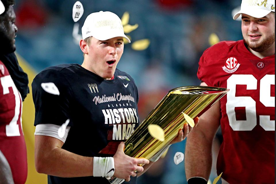 Alabama Crimson Tide quarterback Mac Jones (10) celebrates with the CFP National Championship trophy after beating the Ohio State Buckeyes in the 2021 College Football Playoff National Championship Game.