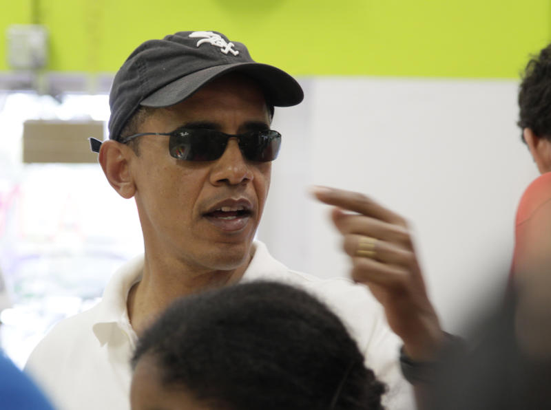 President Barack Obama orders shave ice with family and friends at Island Snow at Kailua Beach Center while on vacation with the first family in Kailua, Hawaii, Monday, Jan. 3, 2011. (AP Photo/Carolyn Kaster)