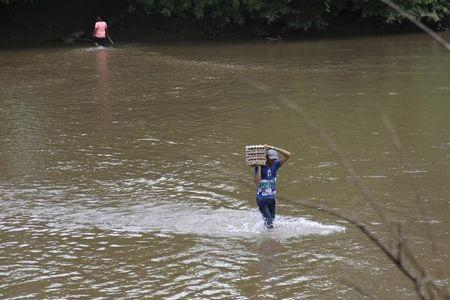 A man carries a carton of eggs across a river in the border town of Boca del Grita in the state of Tachira, Venezuel