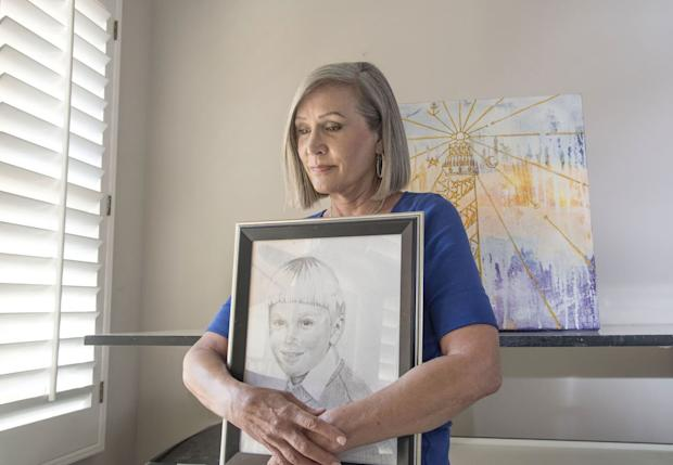 Barbara Van Rooyan holds a portrait she drew of her son, Patrick Stewart, who died at age 24 after taking an OxyContin pill. Patrick, who had also consumed a couple of beers, was opioid intolerant and suffered respiratory failure in his sleep. (Ana Venegas for KHN)