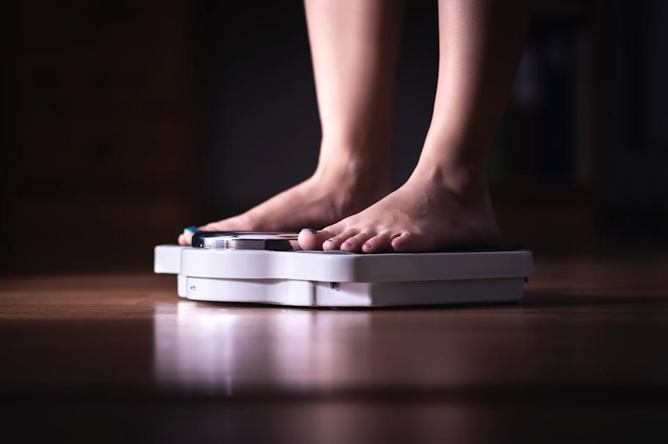 Feet on scale. Weight loss and diet concept. Woman weighing herself. Fitness lady dieting. Weightloss and dietetics. Dark late night mood.