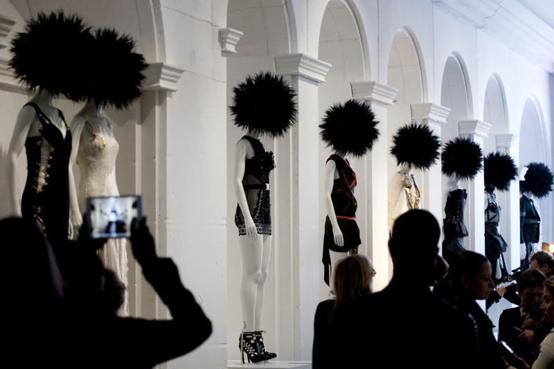 """A visitor photographs the Metropolitan Museum of Art's exhibit, """"Punk: Chaos to Couture,"""" Monday, May 6, 2013 in New York. The show, which examines punk's impact on high fashion from the movement's birth in the 1970s through its continuing influence today, is open May 9 through August 14. (AP Photo/Mark Lennihan)"""
