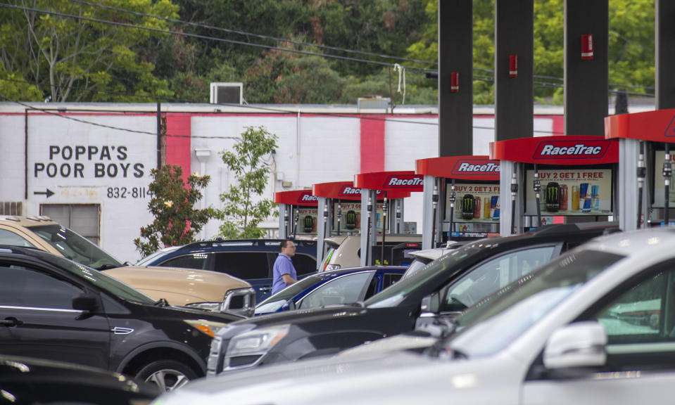 Long lines are seen at a gas station in Jefferson, La., as people prepare for the arrival of Hurricane Ida on Friday, Aug. 27, 2021. Forecasters now say Ida could be a major Category 3 hurricane with top winds of 115 mph when it nears the U.S. coast. (Chris Granger/The Times-Picayune/The New Orleans Advocate via AP)