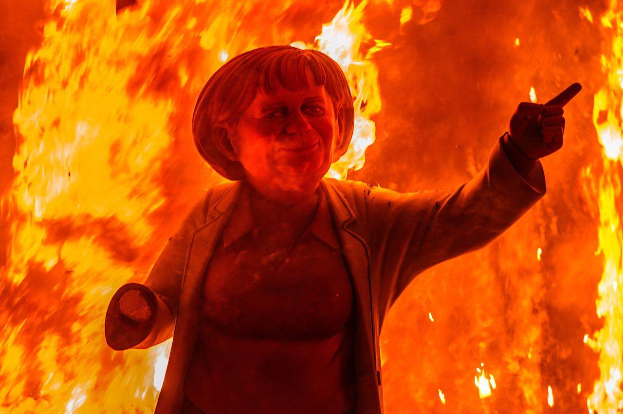 VALENCIA, SPAIN - MARCH 20:  A 'Ninot' (puppet) depicting German Cancellor Angela Merkel burns during the last day of the Las Fallas Festival on March 20, 2013 in Valencia, Spain. The Fallas festival, which runs from March 15 until March 19, celebrates the arrival of spring with fireworks, fiestas and bonfires made by large puppets named Ninots.  (Photo by David Ramos/Getty Images)