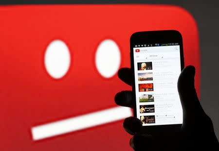 A picture illustration shows YouTube on a cell phone, in front of a YouTube copyright message regarding a video on an LCD screen, in central Bosnian town of Zenica